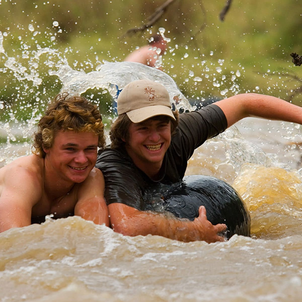 2 young men tubing; holding onto a rubber ring whilst splashing down the river