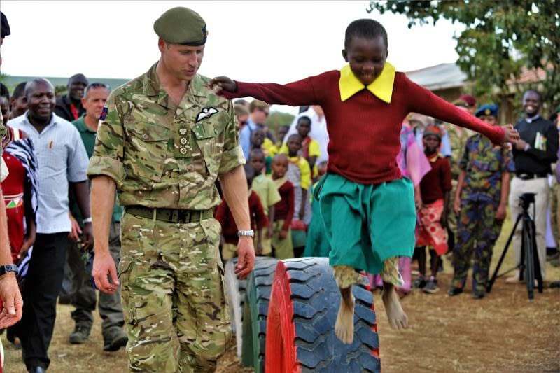 Prince William in army uniform watching a young boy playing and jumping from a tire
