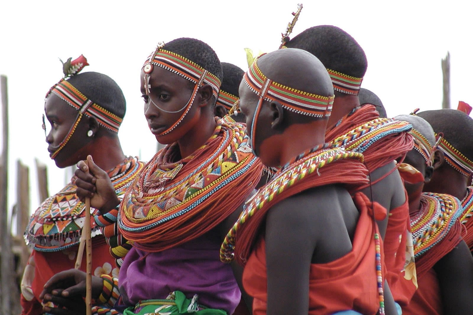 Samburu people dressed in traditional clothing including red, white, green and black headdresses and beaded collars