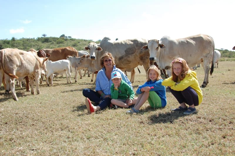 Family sat in front of a herd of Boran cattle
